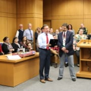 State Attorney Brian Haas presents Pete Mislovic with a plaque during a retirement party..